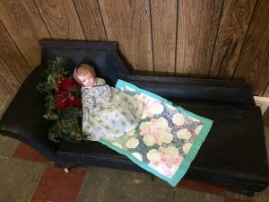 Vintage doll lying on a miniature fainting couch
